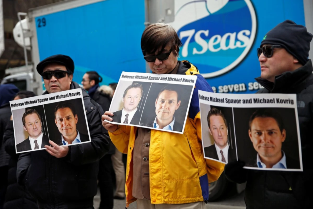 People hold placards calling for China to release Canadian detainees Michael Spavor and Michael Kovrig: SCMP via Reuters